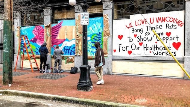 Deux artistes peignent une murale à Vancouver.