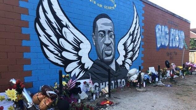 La peinture représente George Floyd avec des ailes d'ange. Les gens ont déposé devant fleurs et ballons.