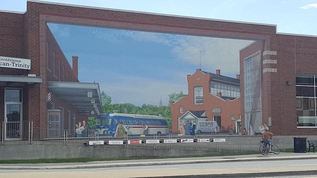 Un terminus d'autobus en trompe-l'oeil sur un mur de briques rouges.