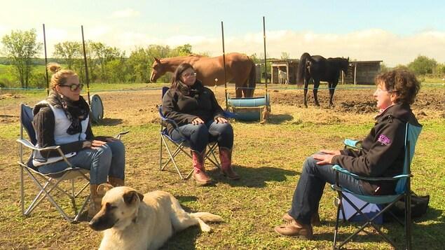 Trois femmes méditent les yeux fermés sur un ranch.