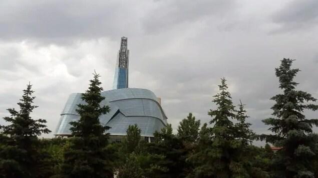Le Musée canadien pour les droits de la personne vu de l'extérieur derrière des arbres.