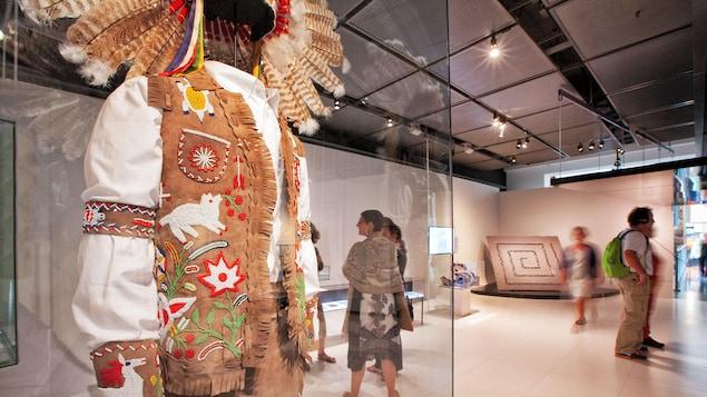 Un vêtement traditionnel autochtone est exposé dans une salle de musée.