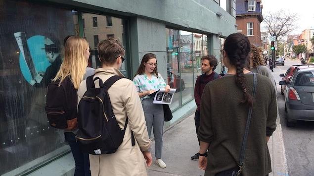 Un groupe de personnes écoute une guide qui fait une visite dans les rues de Montréal.
