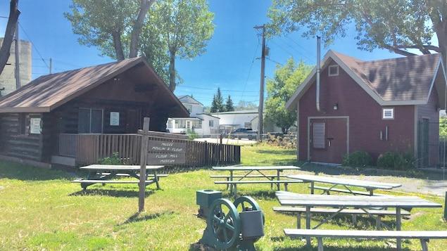 Un moulin, des bancs, une cabane et une maison
