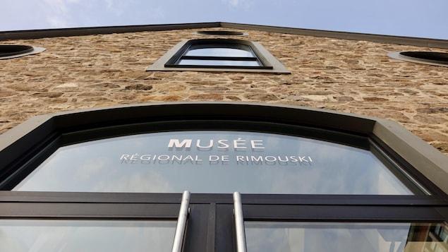 Enseigne en haut d'une porte du Musée régional de Rimouski avec son nom inscrit sur la vitre.