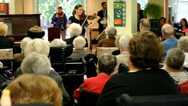 Une violoniste de la Société pour les arts en milieux de santé en plein concert en CHSLD