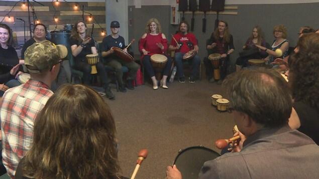Un groupe de personnes est assis en cercle avec des tambours et des djembés.