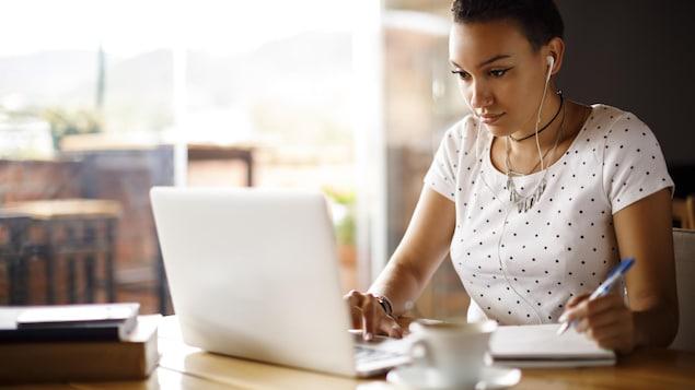Une jeune femme prend des notes en consultant son ordinateur portable. Elle porte des écouteurs dans les oreilles.