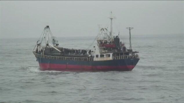 Des dizaines de personnes attendent les secours sur le pont du bateau.