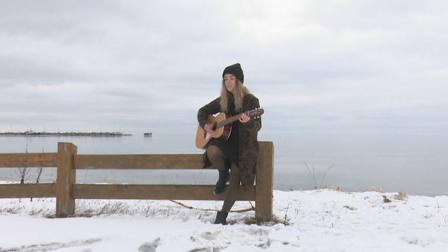 Mylène Vallée chante devant le fleuve en Gaspésie.