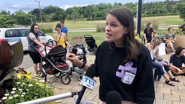 Myriam Lapointe-Gagnon répond aux médias devant l'Hôtel Universel. Elle est accompagnée de plusieurs parents et de leurs enfants.