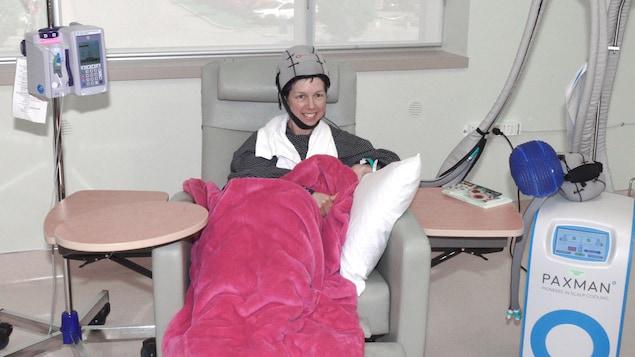 La femme de 42 ans est assise à l'hôpital avec un casque sur la tête.