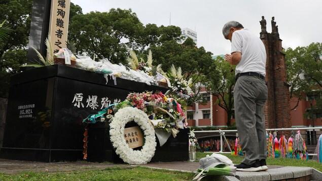 L'homme se tient devant le cénotaphe fleuri.