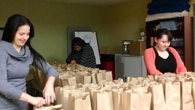 Trois femmes mettent des aliments dans des sacs à lunch