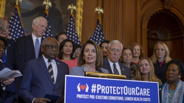 Nancy Pelosi parle derrière un lutrin, de nombreux démocrates sont réunis derrière elle.