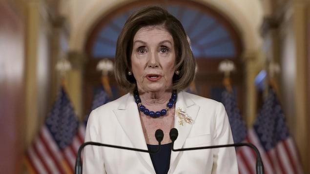 Nancy Pelosi derrière un lutrin avec, derrière elle, des drapeaux des États-Unis.