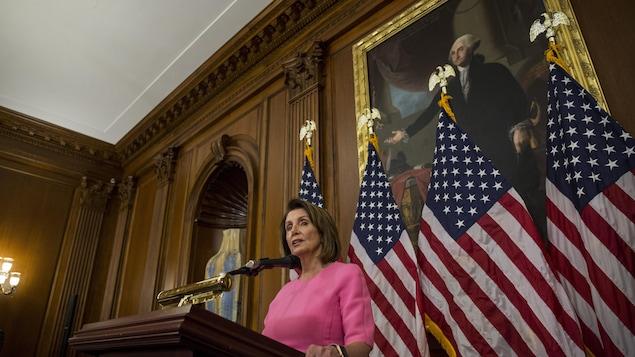 Nancy Pelosi devant des drapeaux des États-Unis.