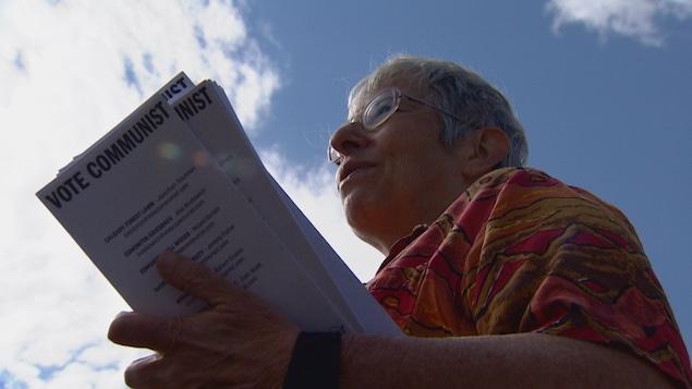 """Naomi Rankin tient des tracts qui disent """"Votez communiste"""" en anglais."""