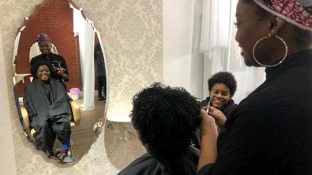 Une jeune femme noire est assise sur une chaise chez une coiffeuse et se regarde dans un miroir.