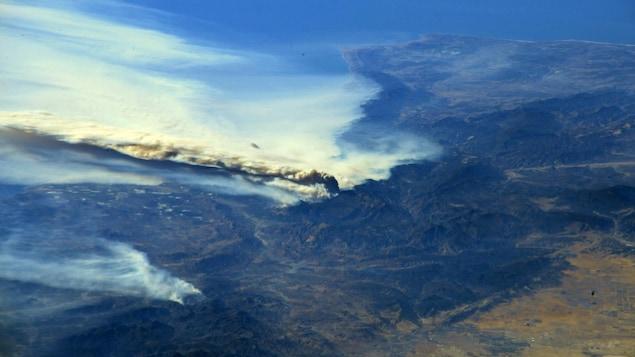 Une photo prise par la Station spatiale internationale montre des énormes panaches de fumée se dégager de la côte de l'État de la Californie.