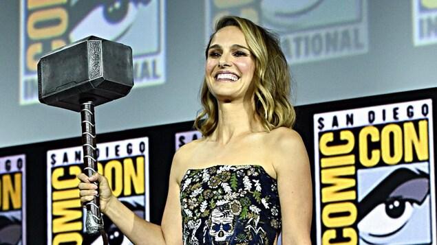 Natalie Portman tient un gros marteau dans la main droite.