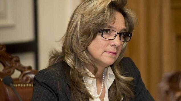 La conseillère assise au conseil municipal.