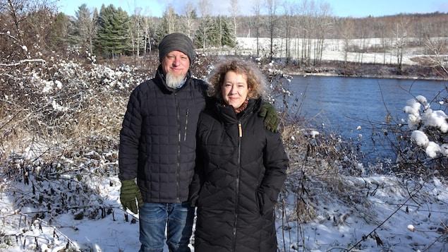 Les deux personnes debout ensemble, près d'une rivière, dans un décor enneigé.