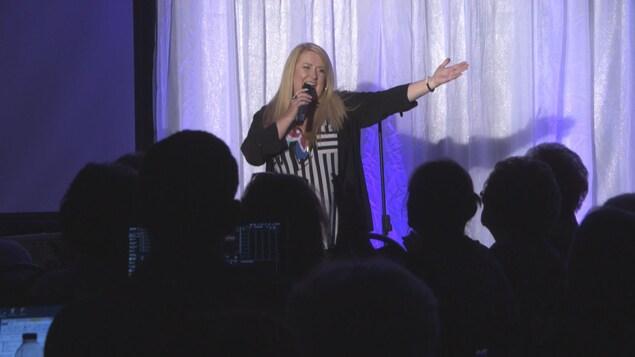 Nathalie Simard chante sur scène devant les spectateurs assistant à sa conférence.