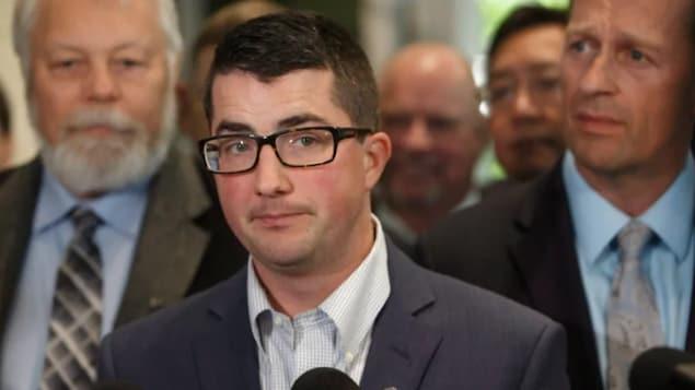 Nathan Cooper parle au micro devant ses collègues du Parti conservateur uni.