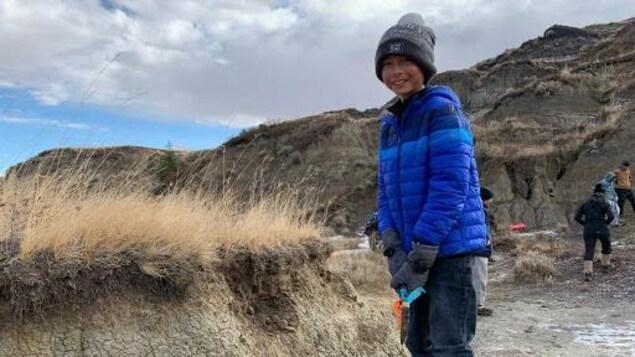 Un jeune enfant, tuque, gant et veste, tient une petite pelle devant le site d'excavation, typique des Badlands albertaines.