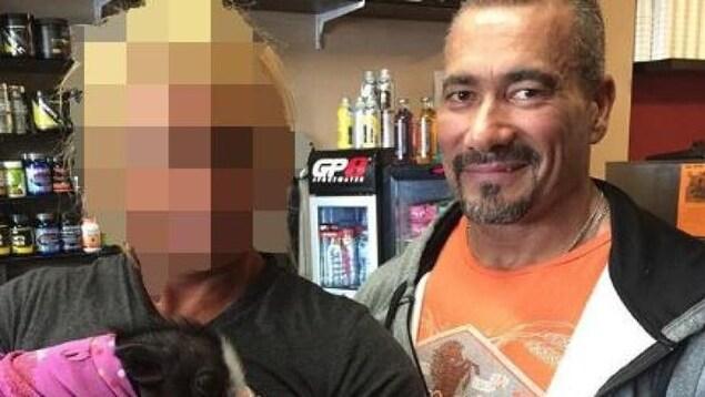 Photographie du policier en compagnie d'une autre personne dont le visage est flouté.