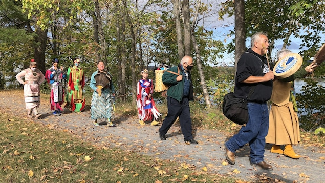 Des Autochtones défilant sur un sentier.