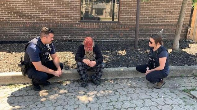 Deux policiers interviennent auprès d'une personne qui est assise sur le trottoir.