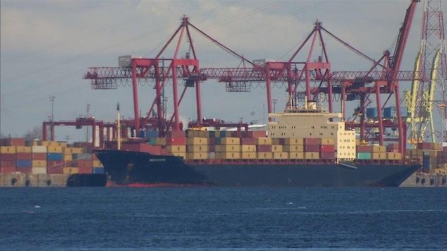 Un navire porte-conteneurs dans le port de Montréal, avec des conteneurs sur le quai