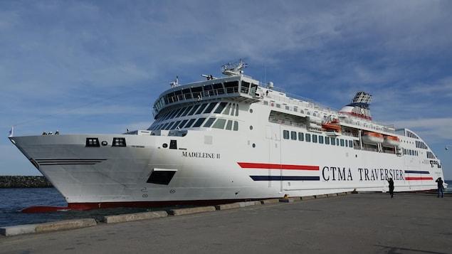 Deux personnes prennent des photos du navire accosté au quai.