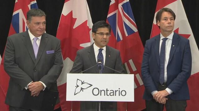 Les trois hommes sont sur un podium.