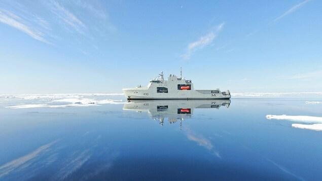 Le NCSM Harry DeWolf navigant sur un océan ou flotte quelques plaques de glace.