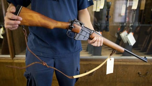 Un homme tient une carabine dans ses mains.