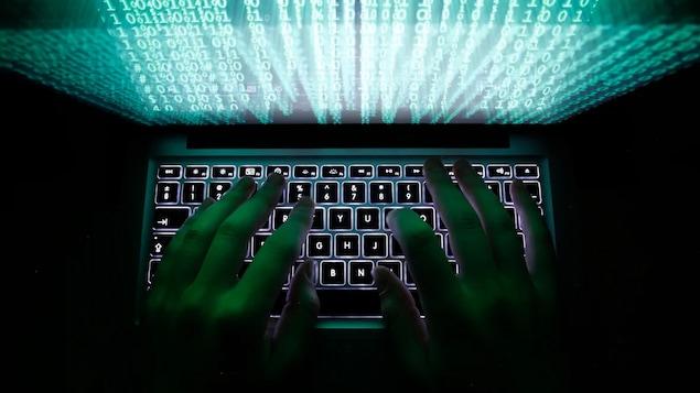 Les mains d'une personne non identifiée tape sur le clavier d'un ordinateur.