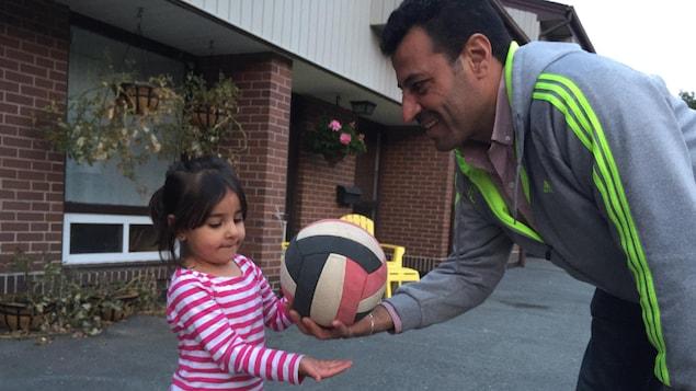 Easa Al-Hariri, qui était dentiste en Syrie, joue avec sa fille, Yara.