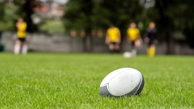 Un ballon de rugby en premier plan avec des joueurs à l'arrière.