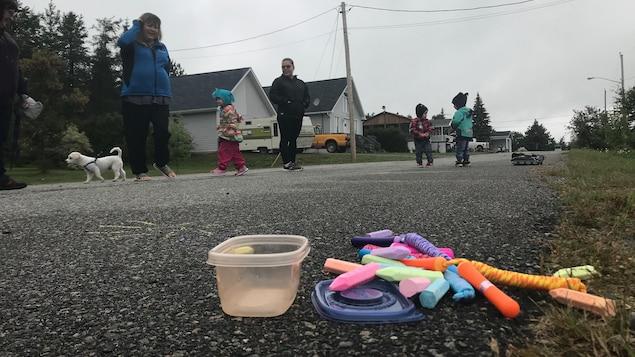 Des enfants et des mamans jouent dans la rue, des craies de marelle posées au sol.