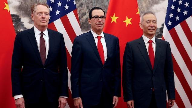 Trois hommes portant des vestons de couleur bleu marin et des cravates rouges posant devant les drapeaux américain et chinois.