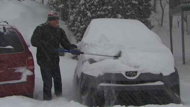 Un homme déneige sa voiture.