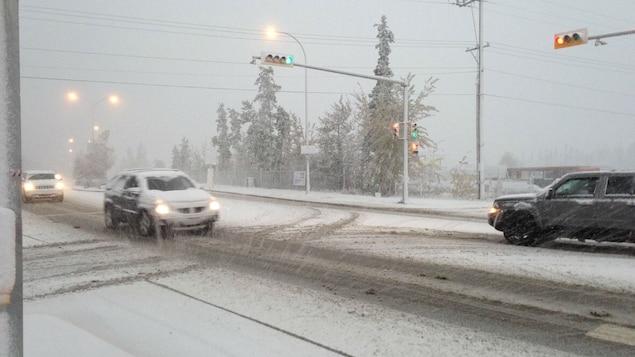 Des voitures avancent doucement sur une route enneigée de Whitehorse.