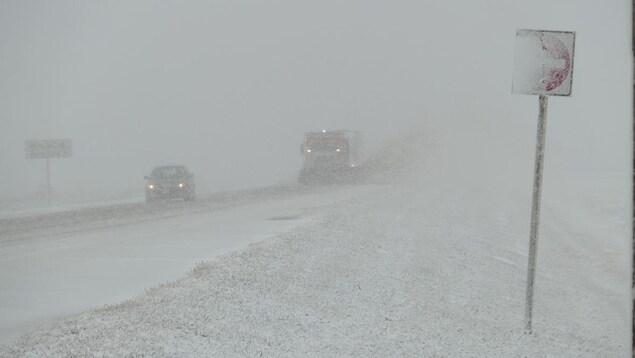 Sur une route enneigée, on distingue à peine les voitures à travers les flocons et le brouillard.