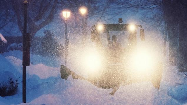 Une déneigeuse déblaie la neige sur un trottoir du quartier nord d'Halifax pendant la nuit.