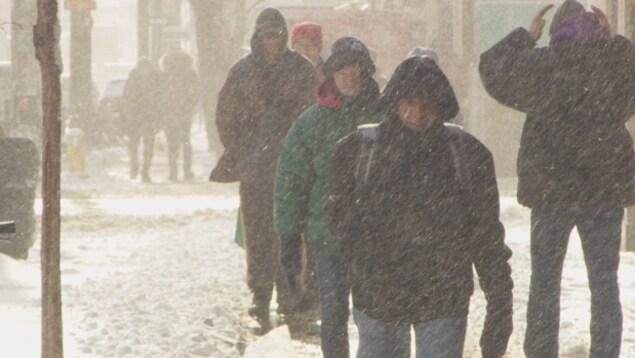 des gens se promènent sur les trottoirs enneigés de Toronto