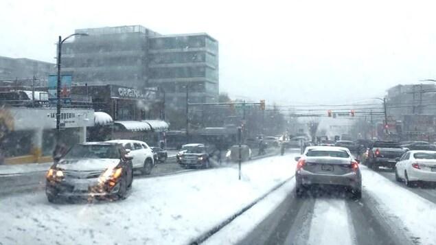 Artère principale très enneigée avec des véhicules circulant dans les deux directions dans des conditions hivernales.
