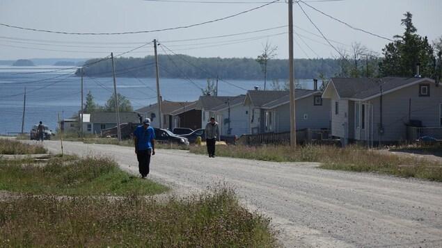Au premier plan, deux personnes qui marchent sur la route, avec, au fond, le lac.